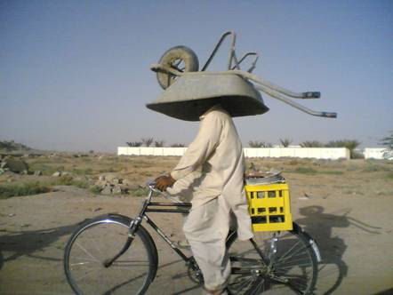 Funny Pictures of Bike Rider with Wheel Barrow on Head