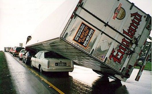 Funny Pictures of Transport Truck Leaning on a Cadillac